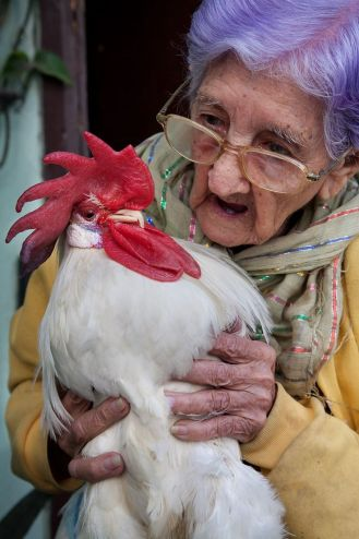 A 95 year old woman with her pet rooster. Havana (La Habana), Cuba